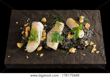 Black cuttlefish ink risotto with lightly grilled calamari on wooden board