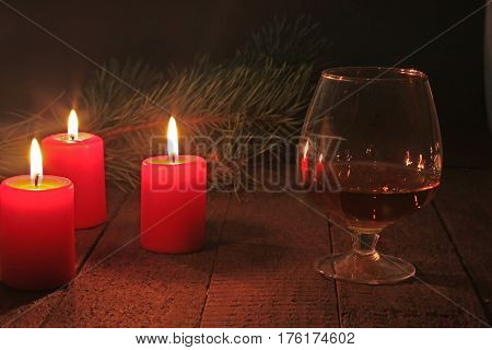 Glass of brandy or cognac and candle on the wooden table. Celebration composition