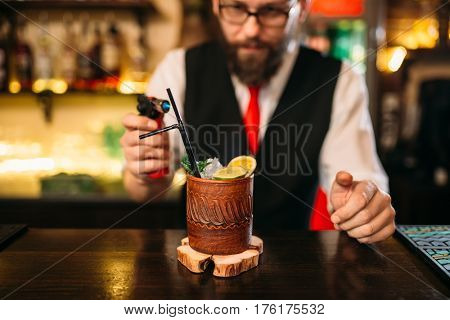 Bartender making alcohol beverage with gas burner