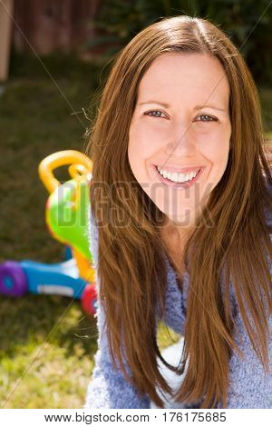 Portrait of a mother smiling and sitting outside.