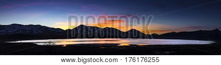 Desert lake flooded playa at Sunset with mountain ranges and colorful clouds. White Lake Cold Springs Nevada