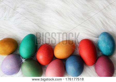 A variety of different colored and sized painted easter eggs are framing the bottom border of a fur white background for copy-space.