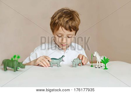 Little boy is playing with toy African animals. childhood. Learning concept