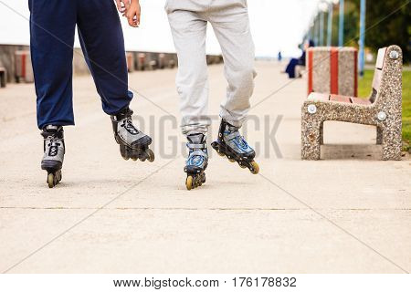 Spending free time together in summer. Hobby and lifestyle. Exercising and healthy body. Close up of legs in sportswear riding rollerblades.