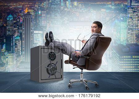 Businessman resting putting leg on safe