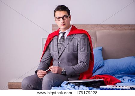 Superhero businessman working from his bed