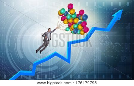 Businessman flying on balloons over graph