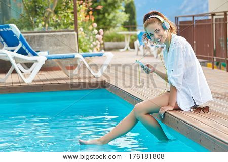 Happy smartphone woman relaxing near swimming pool listening with earbuds to streaming music. Beautiful girl using her mobile phone