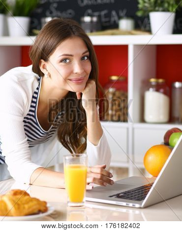 Attractive young woman using laptop and sitting in the kitchen