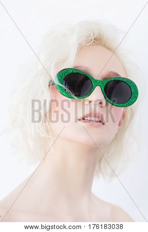 Glamour portrait of beautiful blonde woman. Nude make up. A blonde woman with short and wavy hair. Everyday make-up.Woman in green sunglasses