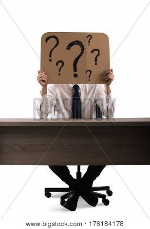 Businessman in the office holds a cardboard with question marks