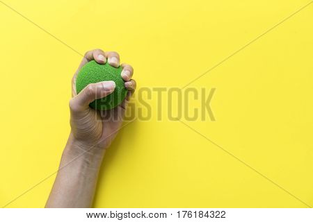 hand of woman holding stress ball on yellow background