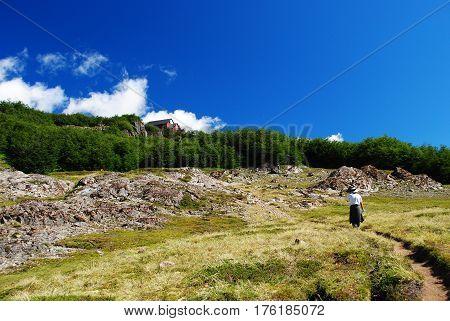 A man walking to a mountain shelter / A day hike to a mountain retreat