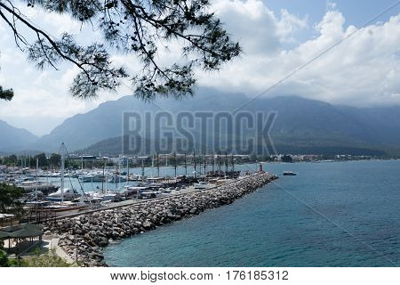 KEMER, TURKEY - APRIL 25 View of yacht marina and mountains with turqoise sea and cloudy sky IN 2016