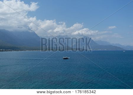 KEMER, TURKEY - APRIL 25 View of sea and beautiful high mountains descending to sea with small touristic boat and cloudy sky 2016