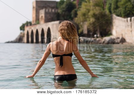 Backview portrait of fit blonde female standing in sea in front of Alanya medieval shipyard wearing black bikini with arches shot on sunny day