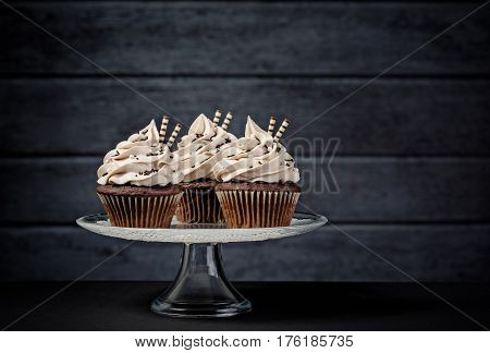 Three chocolate cupcakes with buttercream icing on a cake stand