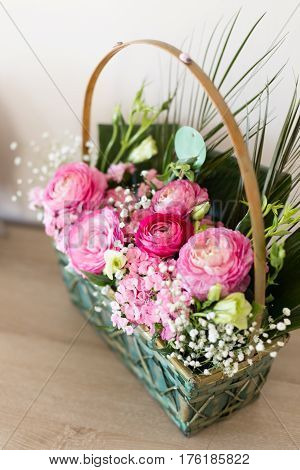 Flower arrangement in basket with dark and light pink ranunculus and austeria view from above with central flowers in focus and other flowers blurred