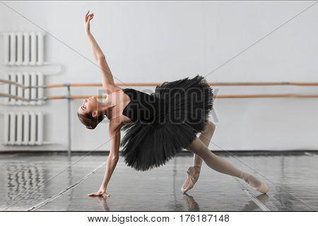 Beautiful ballerina sit on the twine in class