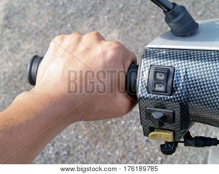 closeup man's hand rider holding motorcycle handlebar