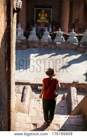Tourist Woman in hat and photo camera in ancient Buddhist complex in Ayutthaya Historical Park Thailand