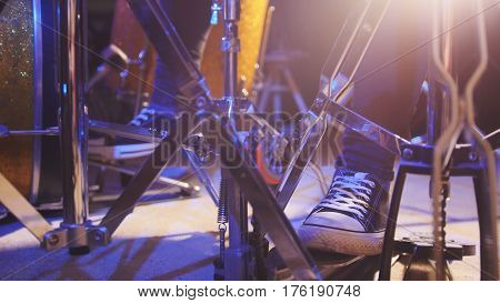 Drummer's foot wears sneakers moving drum bass pedal, close up