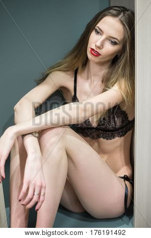 Young brunette Woman sits in a cupboard in the bedroom at home.