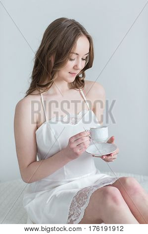 Young girl with Cup of coffee in the bedroom in the morning.