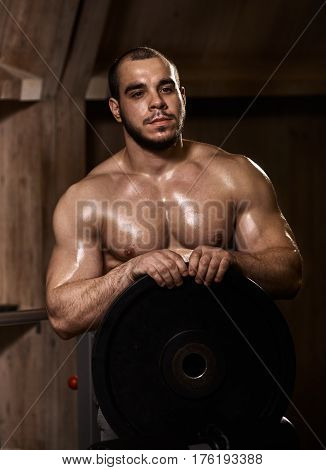 muscular man preparing for training and holding bumper plate