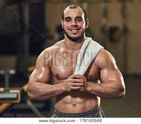 Portrait of young happy tired muscular sportsman with towel
