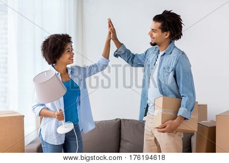 people, repair and real estate concept - smiling couple with cardboard boxes and lamp moving in or out of home and making high five