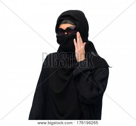 accessory, fashion and people concept - muslim woman in hijab and sunglasses over white background