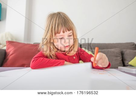 Blonde Child Drawing On White Paper