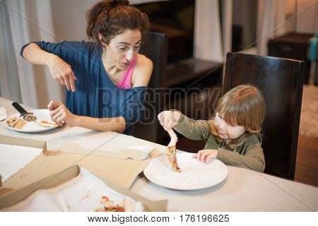 Child Playing With A Pizza Piece With Mothe