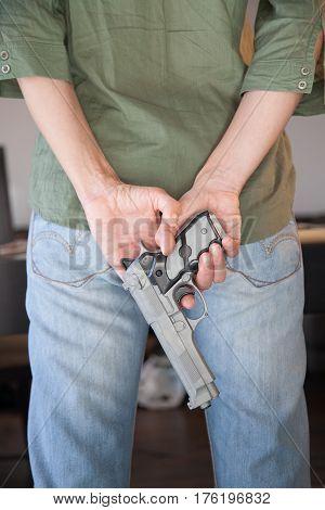 Gun In Hands Behind Back
