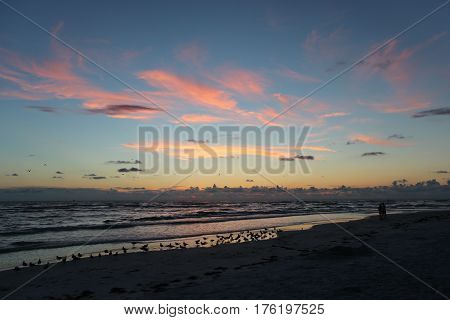 The beach on Lido Key, Sarasota, Florida just after sunset, with wispy clouds turning pink and yellow against blue sky.