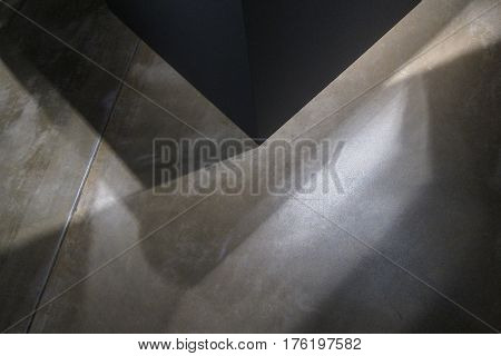 Strange shadows cast on a building's cement floor, creating abstract patterns, intriguing background.