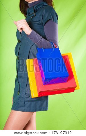 Woman Holding With Arm Shopping Bags On Green Background