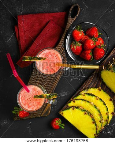 Summer Fruit cocktail smoothie with strawberries and pineapple in the glasses. Ingredients for cocktail smoothie of fresh strawberries and pineapple. Dark black background. Top view from above and copy space.