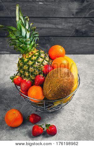 Exotic tropical fruit pineapple coconut berries strawberries mandarins clementines bananas in metal bowl basket of fruit on gray background.