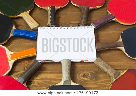 Clean notebook in the center of an object for ping pong on a wooden background