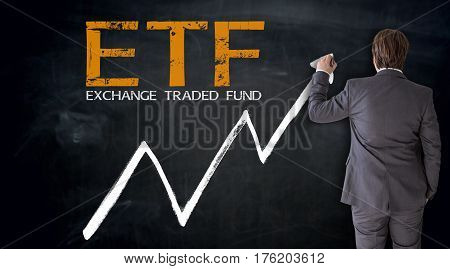 Businessman writing ETF on blackboard concept picture