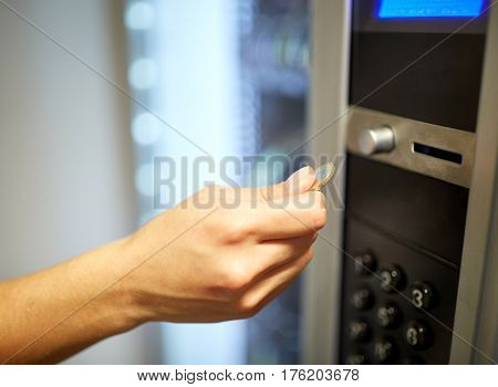 sell, technology, people, finances and consumption concept - hand inserting euro coin to vending machine