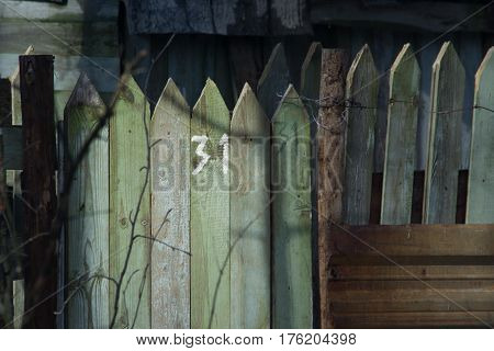 Wooden fence, with the number of the plot