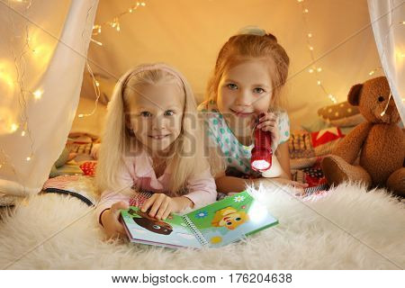 Cute little girls reading book in hovel at home