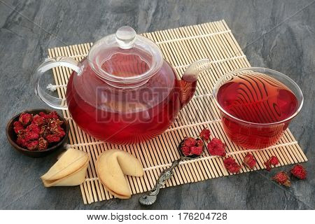 Pomegranate flower tea in a glass teapot and cup, with old spoon and fortune cookies on bamboo mat.