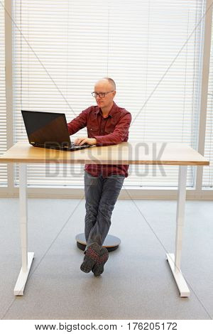 ergonomics in office work -  man at the desk on pneumatic stool