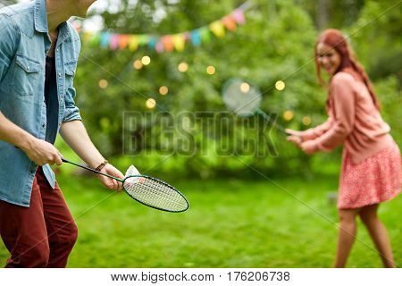 leisure, holidays, people and sport concept - happy couple playing badminton or shuttlecock at summer garden