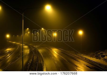 Foggy empty highway with street lights at night.