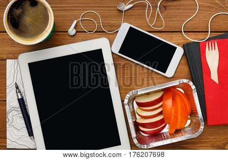 Healthy lunch at workplace with copy space on tablet pc. Top view flat lay of desktop fruit snack in foil container and mobile phone on wooden desk background